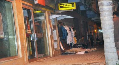 صورة اليوم: بائع مُتَجَوّل يستغل واجهة بنكية لعرض بضاعته