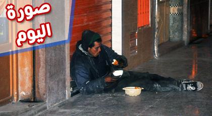 صورة اليوم : متشرد يأكل وجبة عشائه في العراء مفرشا الأرض خارج المطعم
