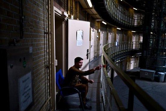 أحد اللاجئين يرتشف الشاي أمام غرفته بالسجن