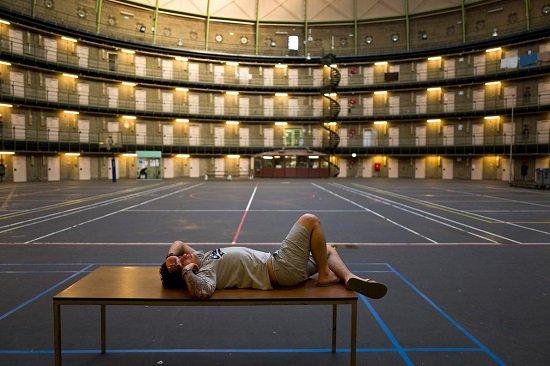 واحد من اللاجئين يستلقى باسترخاء داخل ملعب السجن