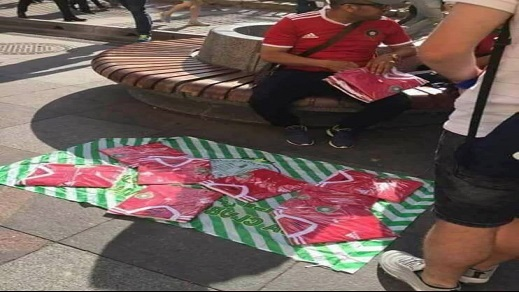 """من طرائف المونديال: فراش مغربي يعرض قمصان """"الأسود"""" للبيع على الرصيف بروسيا"""
