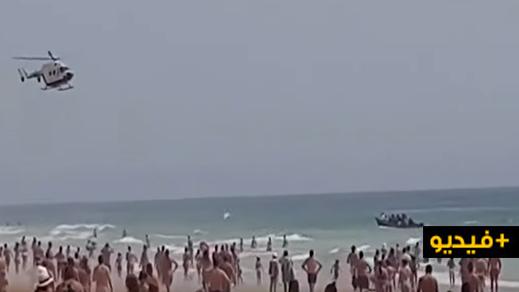 شاهدوا.. زورقٌ للمهاجرين المغاربة يرسو على شاطئ إسباني وسط آلاف السياح